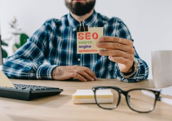 A man at a desk holding a post-it note with SEO on it