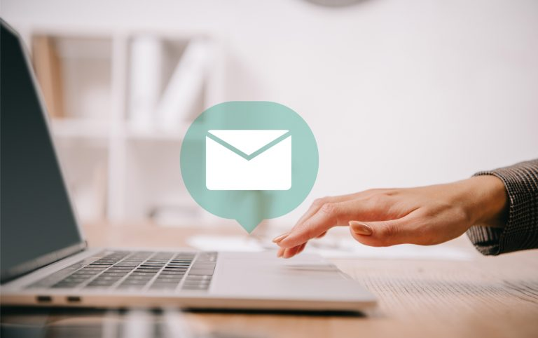 A hand using a laptop trackpad for email marketing