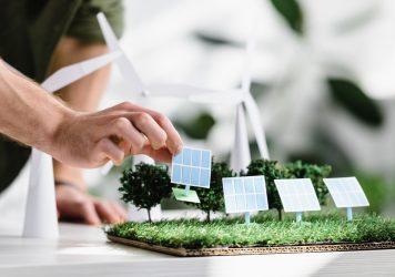 A solar installer placing panels on a grass model