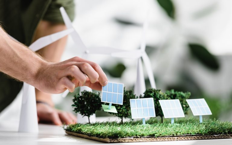 A solar installer placing panels on a grass model