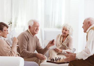 A group of seniors playing chess - marketing for senior living