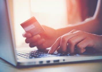 A person entering a credit card on a laptop - convert website traffic