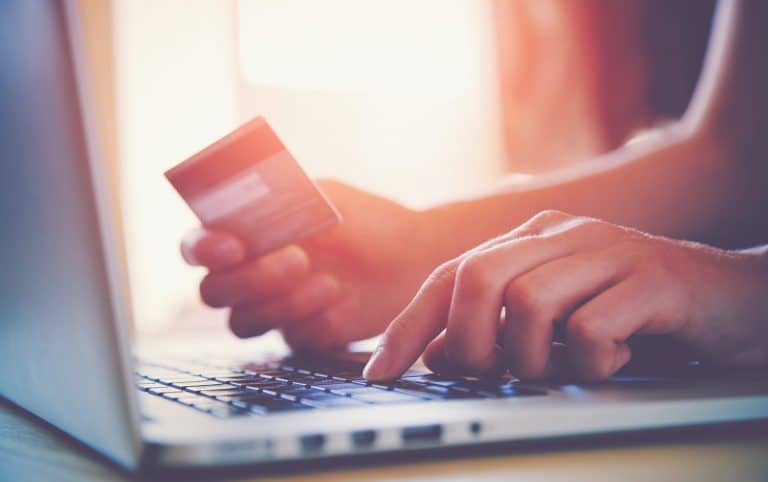 A person entering a credit card on a laptop - convert website traffic into sales