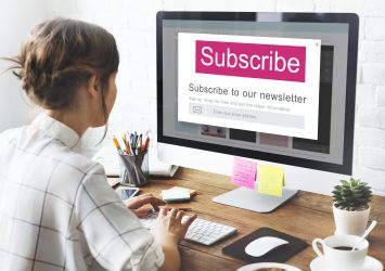 A person sitting at a desktop looking at a newsletter subscription form - tips on how to generate more leads