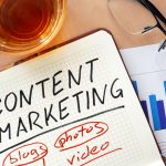 """A journal with the words """"content marketing,"""" """"blogs,"""" """"photos,"""" and """"video"""" written on it"""
