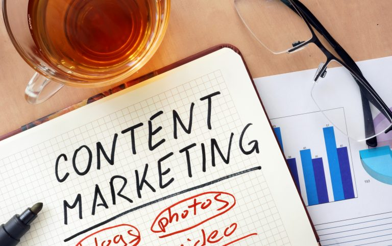 "A journal with the words ""content marketing,"" ""blogs,"" ""photos,"" and ""video"" written on it"