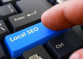 "A finger pressing a keyboard key that says ""local SEO"""