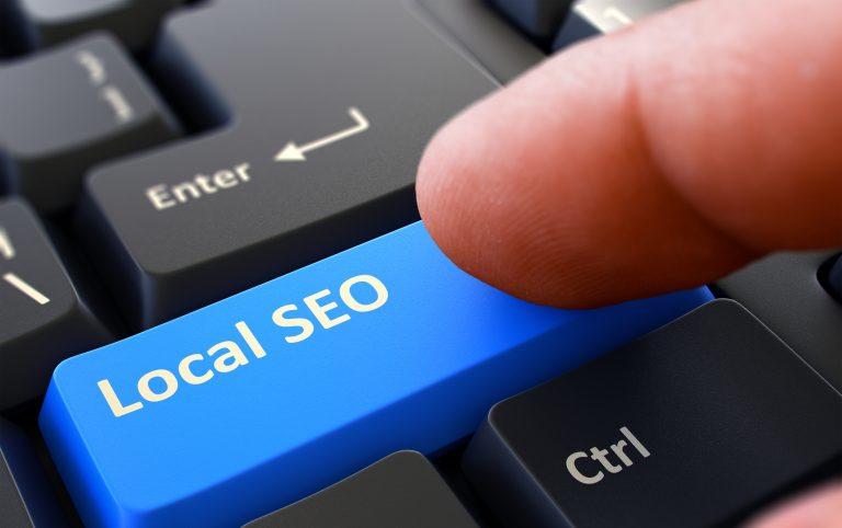 "A finger pressing a keyboard key that says ""local SEO"""