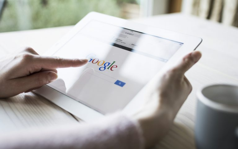 A person holding a tablet open to a Google search page - is SEO right for your small business?