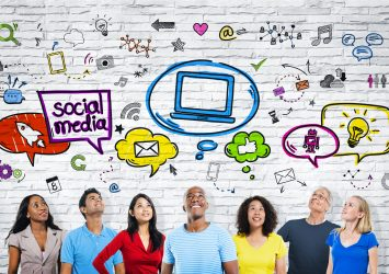 People in front of a white brick wall looking up at social media and marketing icons