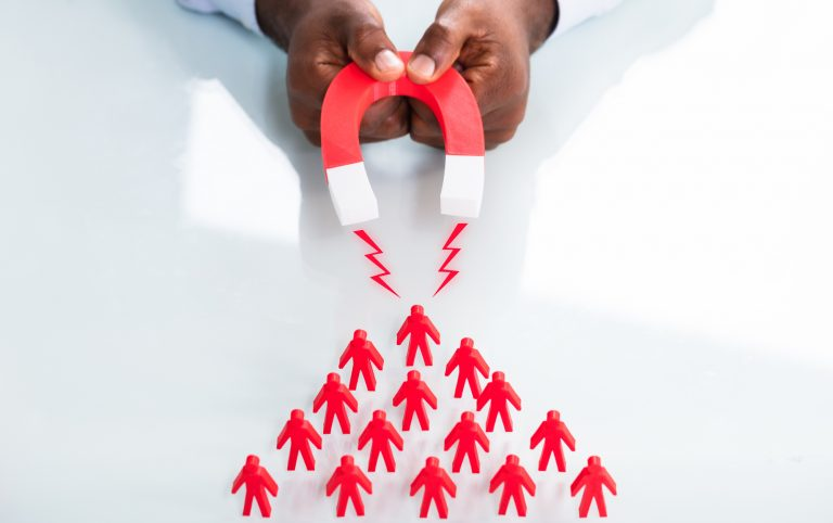A person holding a magnet that's attracting red figures of people - representing a lead magnet