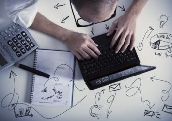 A man sitting at a laptop with drawings on the tabletop around it - representing effective email marketing.