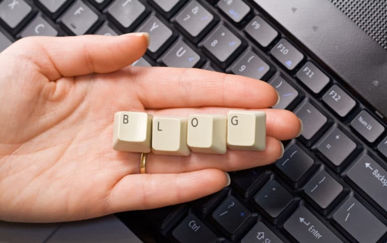 "A person's hand in front of a keyboard, holding keys that spell out ""blog."" This post covers how to make a post on WordPress."