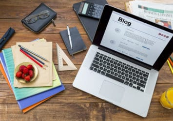 """A desk with a bowl of fruit and a computer that displays the word """"blog,"""" representing an effective small business blog."""