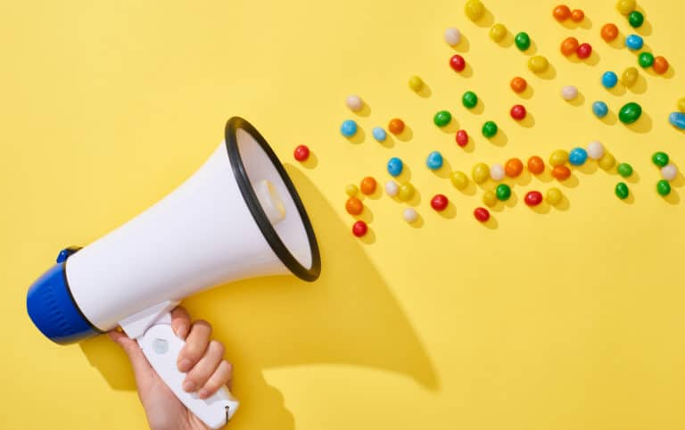 A person's hand holding a megaphone with colorful candies coming out, representing paid ads for small businesses.