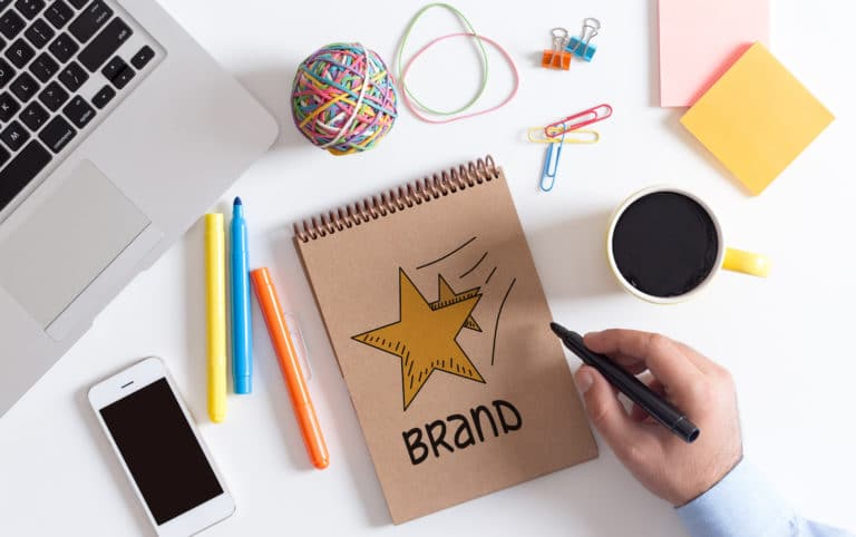 """A work desk with a person's hand drawing a star on a notepad with the word """"brand"""", representing building a brand voice."""