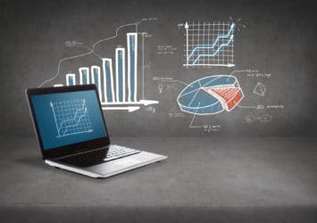 A laptop on a table in front of a bar chart, line graph, and pie chart, representing monitoring your marketing analytics.