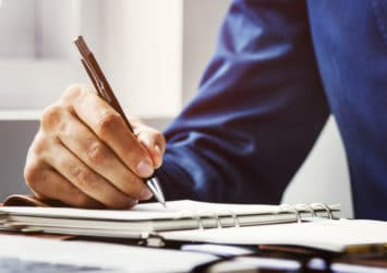 A close-up of a person's hand writing in a notebook, representing planning an effective lead magnet.