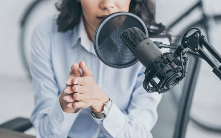 A person seated at a table speaking into a microphone for a radio or podcast show, representing speaking your audience's language