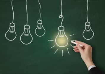 A chalkboard with light bulbs drawn on it, with one glowing, representing finding the right channel for lead generation