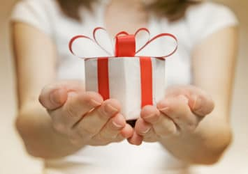 A person holding out their hands toward you, holding a present, representing delivering relevant content to your leads.