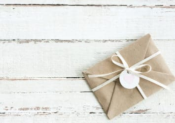 A letter wrapped with a bow, representing distributing lead magnets