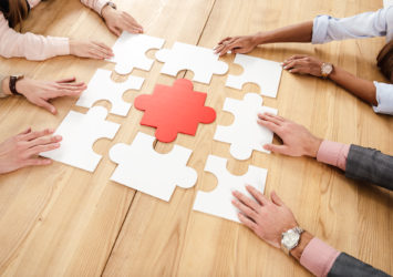 A group of people at a desk looking at large puzzle pieces with a red colored piece in the center