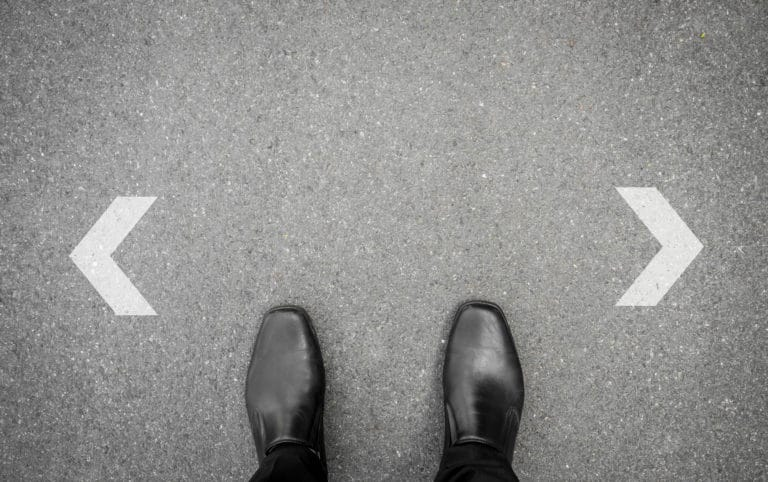 Two business shoes facing arrows to the left and right, representing a decision to move down the lead funnel