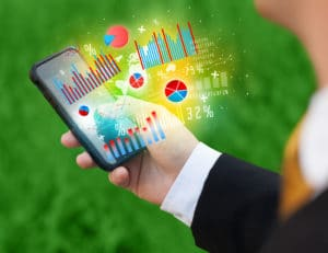 A person holding a mobile phone with charts coming out of it