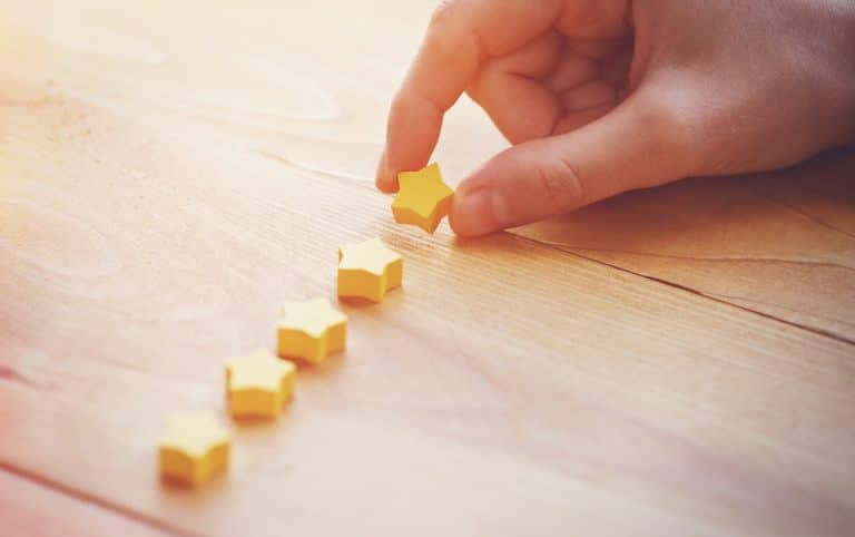 A hand laying 5 star blocks on a wooden table, representing good reviews