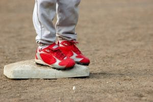Two cleats on a little league player's feet standing on a baseball base