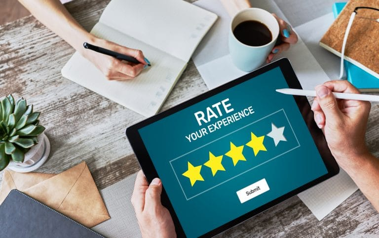 """A person's hands holding a tablet with a """"Rate Your Experience"""" screen, about to leave a review"""