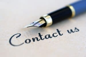 """A fountain pen next to a handwritten """"contact us"""""""
