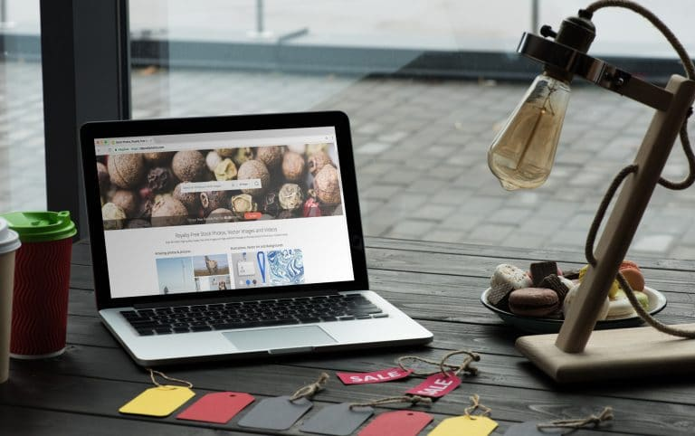 A laptop sitting on a desk with sales tags in front of it and an industrial style lamp next to it
