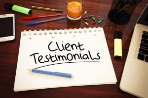 """A notepad on a desk with the words """"Client Testimonials"""" written on it"""